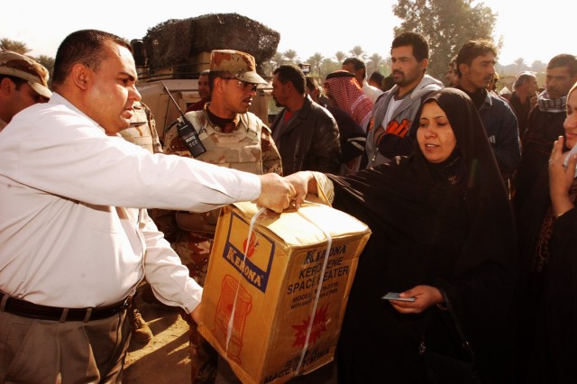 A resident of the Quds Camp in central Baghdad receives a heater from Janeen Neighborhood Advisory Council chairman Udai Ra'ed, during a humanitarian aid mission conducted by Soldiers from 3rd Battalion, 82nd Field Artillery Regiment, 2nd Brigade Combat Team, 1st Cavalry Division, Iraqi Army troops and the local NAC, Nov. 29.