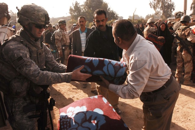 Capt. Todd Martin, Battery A, 3rd Battalion, 82nd Field Artillery Regiment, 2nd Brigade Combat Team, 1st Cavalry Division, hands a wool blanket to Janeen Neighborhood Advisory Council chairman Udai Ra'ed, for distribution to a resident of the Quds Camp during a humanitarian aid mission in the central Baghdad neighborhood, Nov. 29.