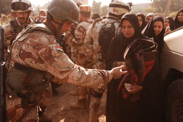 A resident of the Quds Camp in the central Baghdad Janeen neighborhood receives a wool blanket from an Iraqi Army soldier during a blanket and kerosene heater distribution mission conducted by Soldiers from 3rd Battalion, 82nd Field Artillery Regiment, 2nd Brigade Combat Team, 1st Cavalry Division, the Iraqi Army and the local NAC.