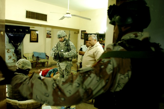 "Fresno, Calif., native Staff Sgt. Joaquin Reyna, Troop O, 4th Squadron, 2nd Stryker Cavalry Regiment, speaks to a resident in central Baghdad during one of the clearing operations of ""Saber Sweep."""