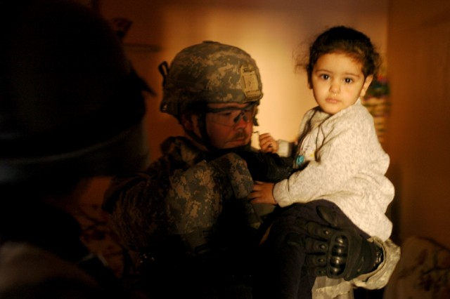 Staff Sgt. Richard Edison, Troop O, 4th Squadron, 2nd Stryker Cavalry Regiment, holds a child during a clearing operation of apartments in Baghdad's Karkh District.