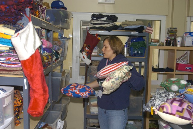 Jenny Clayton stocks shelves at the Wounded Warrior Ministry Center which is benefitting from a holiday increase in donations to servicemembers wounded downrange. Clayton is one of 22 volunteers who donate more than 600 hours a month at the center.