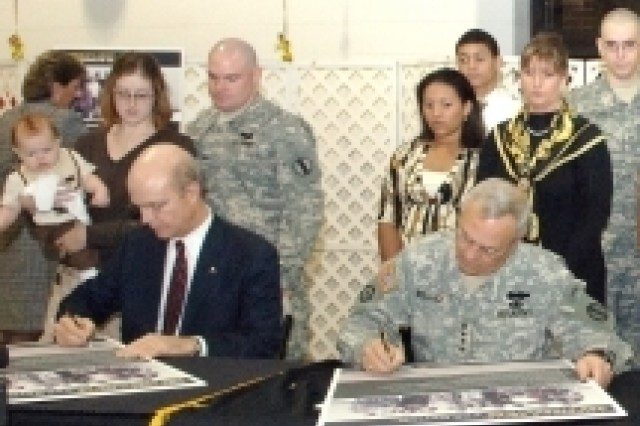 Secretary of the Army Pete Geren, left, and the TRADOC Commanding General, Gen. William S. Wallace, right, sign the Army Family Covenant at Fort Monroe, Va., Nov. 29.