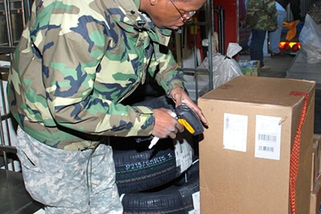 Spc. Alvin Bethea, 566th Postal Company, scans incoming mail Nov. 26 at the Stuttgart Regional Post Office.