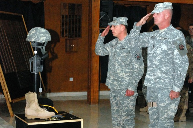 Gen. David Petraeus, commanding general of Multi-National Force - Iraq, and Command Sergeant Major Neil Ciotola, the command sergeant major for Multi-Natinal Corps-Iraq, render a hand salute honoring fallen Soldiers at the Multi-National Division memorial service in the Division Chapel at Camp Liberty in western Baghdad, Dec. 7.