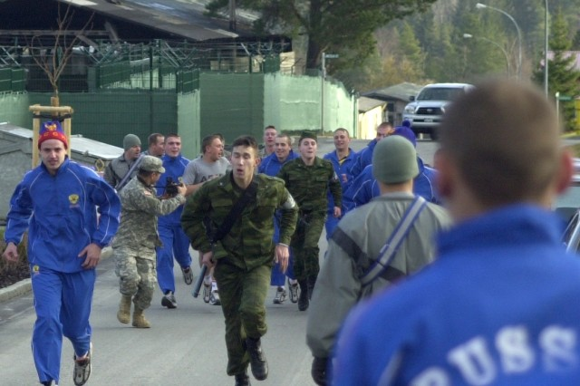 "U.S. and Russian Soldiers in physical training gear cheer on their fellow Soldiers in uniform headed for the finish line of the run and shoot competition that was part of the Dec. 8 ""cultural day"" activities at Hohenfels, Germany, during this week's 2007 Torgau exercise."