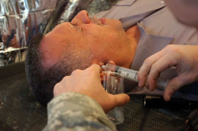 Citrus Heights, Calif., native Spc. Jory Ryland with Company C, 15th Brigade Support Battalion, 2nd Brigade Combat Team, 1st Cavalry Division, irrigates an infected ear canal of a security guard during a cooperative medical engagement hosted by troops from the Black Jack Brigade at the Baghdad Zoo December 4.