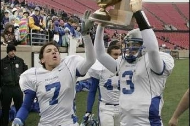 Fort Campbell's Sean Tighe and quarterback C. J. Croft carry the Championship trophy after they defeated Newport Central Catholic during the class 2A State Championship in Louisville Saturday. The Falcons won the championship 21-7.