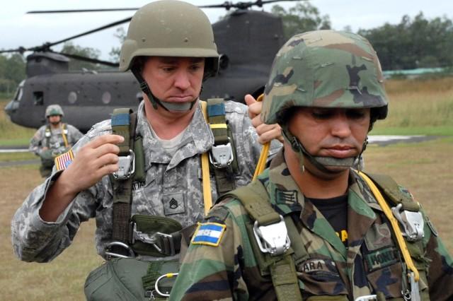 Staff Sgt. David Hattan checks the parachute of Capt. Erwin Lara, an instructor with the Honduran Army.
