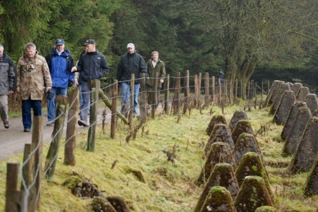"""Members of the U.S. Army Garrison Heidelberg staff walk along a string of anti-tank barriers known as """"dragon teeth,"""" which were built by the German Army along Belgium's border."""