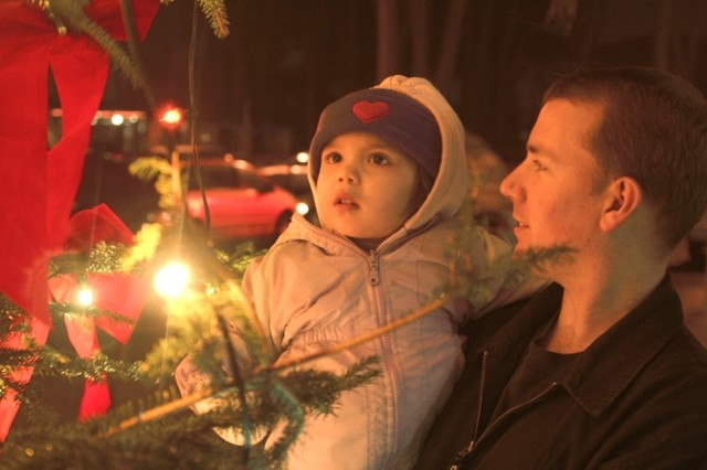 Emily Wooldridge, 2, gazes in wonderment at the Camp Darby Christmas tree with her father, Senior Airman Joseph Wooldridge. The 30-foot tree was donated by the Pistoia Province of Italy.