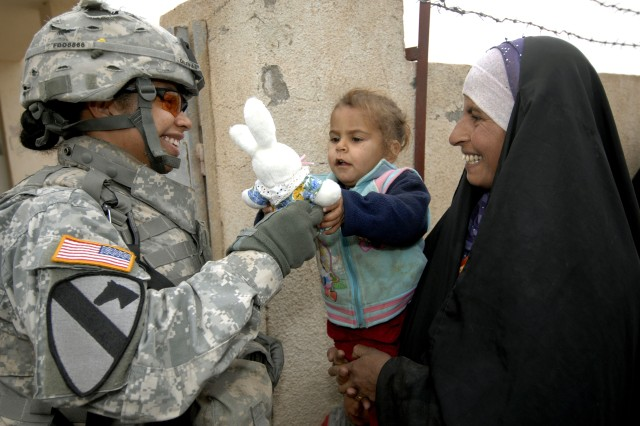 Spc. Deidre Olivas gives a toy to an Iraqi child waiting for medical treatment during a combined medical mission in Quadria, Dec. 7. Spc. Olivas is from Forward Support Troop, 1st Squadron, 7th Cavalry Regiment.