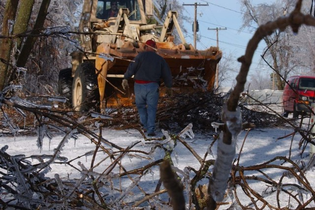 Lynn Wey (foreground) and Al Stevens, both of Fort Riley Directorate of Public Works, load up downed tree limbs Thursday, Dec. 13, in Fort Riley's Peterson Place neighborhood. Monday night's ice storm hit the Peterson area especially hard, knocking out power to most of its residents.