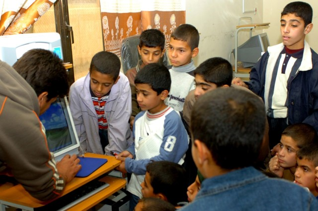 A computer instructor (left) teaches boys ages 11 to early teens how to use a computer during a computer literacy course at the community center in Assiriyah, Iraq Dec. 6.