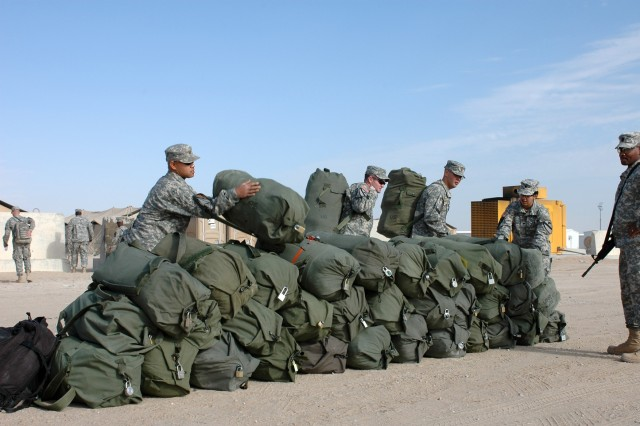 "Soldiers from the 1st ""Attack"" Battalion, 227th Aviation Regiment, 1st Air Cavalry Brigade, 1st Cavalry Division, build a wall of duffle bags as they prepare to move from Camp Virginia, Kuwait, to Ali Al Saleem Air Base and then on to Kuwait City where they'll board a plane headed home to Fort Hood, Texas. While at Camp Virginia waiting for their flight date, the 1st ACB node personnel ensure the troopers' paperwork is in order and that they have accountability of all sensitive items. The node personnel also track all flights with 1st ACB Soldiers on them that fly in and out of Kuwait."