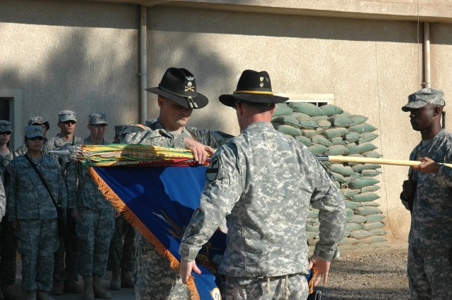 "Lt. Col. Christopher Joslin, commander of 2nd ""Lobo"" Battalion, 227th Aviation Regiment, 1st Air Cavalry Brigade, 1st Cavalry Division, (left), and 1st Sgt. Terrance O'Neal, the acting battalion command sergeant major, (center), case the unit's colors in a ceremony Dec. 10 at Taji, Iraq. Most of the battalion's Soldiers will return to Fort Hood, Texas, by Christmas, with the entire battalion getting home by mid January."""
