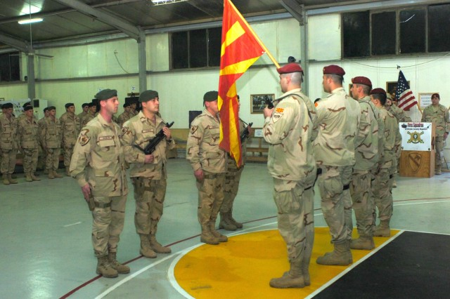 "Macedonian Special Forces soldiers from the outgoing Macedonian ""Wolves"" Team Rotation 9 (right in red berets) prepare to hand the Macedonian national colors to the incoming Macedonian Rangers (left) of Macedonian Team Rotation 10 during a transfer of authority ceremony at Camp Taji, Iraq Dec. 12. The troops from the Macedonian ""Wolves"" Special Forces Battalion spent a six-month tour in Iraq working alongside the Iraqi Security Forces and U.S. troops from the Fires Squadron, 2nd Stryker Cavalry Regiment during joint operations."