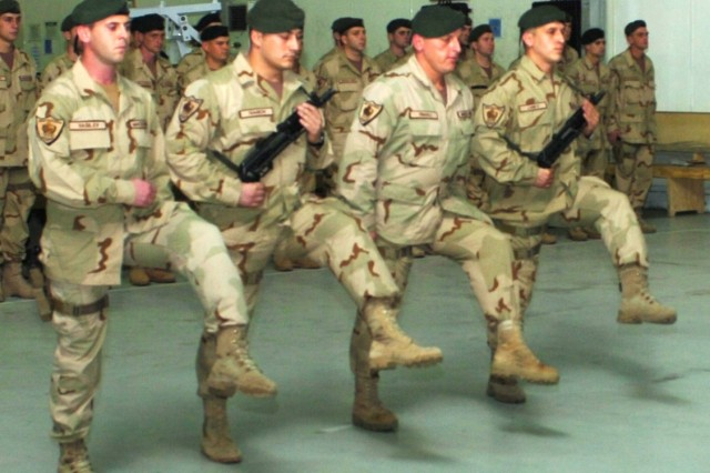 "During a transfer of authority ceremony, incoming Macedonian Rangers of the Macedonian Special Forces march to the spot where they will receive the Macedonian national colors from the Macedonian ""Wolves"" Special Forces Battalion at Camp Taji, Iraq Dec. 12 thereby accepting responsibility for their area of operations for their six month deployment to Iraq."