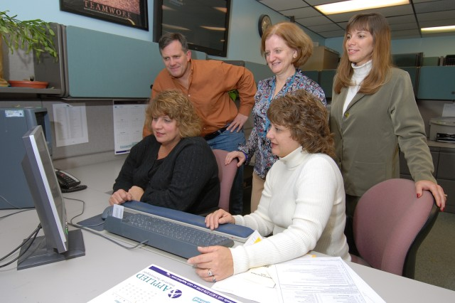 Information Management Directorate employees review one of three software applications they developed that were requested by other installations.  From left, seated: Timi Robertson and Audrey Bandru; standing: Larry Trygar, Ruth Wood and Cathy Fulk.  Missing is Frank Chabala.