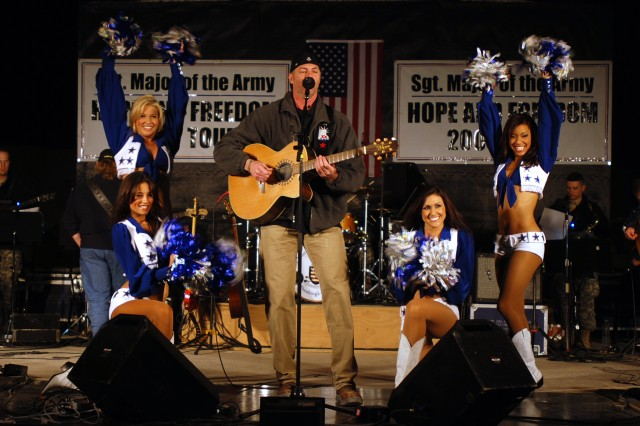 Singer Darryl Worley performs with the Dallas Cowboys Cheerleaders during the Sergeant Major of the Army Hope and Freedom tour, Dec. 16, at Camp Striker, Baghdad.