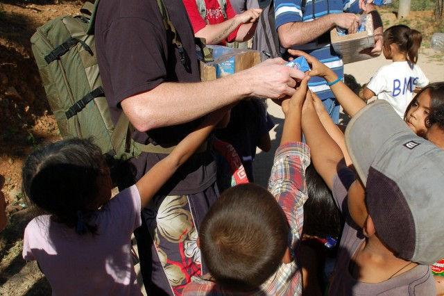 Air Force Staff Sgt. Charles Alford hands milk to a crowd of children in the village of Capiro Dec.