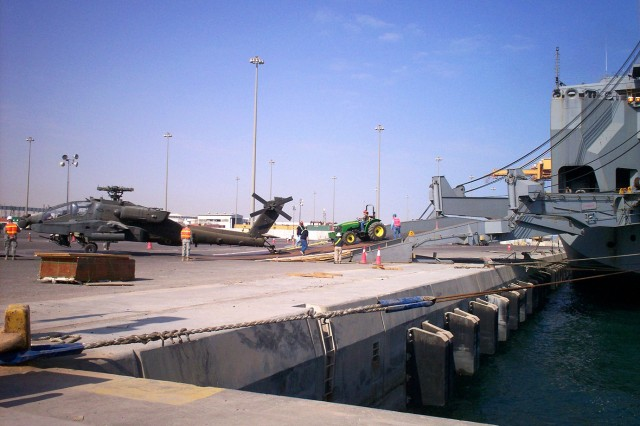 "SHUAIBA PORT, Kuwait - Soldiers from the 1st Air Cavalry ""Warrior"" Brigade, 1st Cavalry Division, and civilian contractors load up AH-64D Apache attack helicopters onto a U.S. Navy ship at Shuaiba Port, Kuwait, Dec. 15. Loading the Apaches onto the ship is the last step of many when transporting the aircraft from Iraq to the United States. Before the aircraft make it onto the ship, they have to be flown to Kuwait, taken apart, cleaned and then inspected by customs officials, said Little Valley, N.Y., native Chief Warrant Officer Scott Hahn, the mobility warrant officer for 1st ACB."