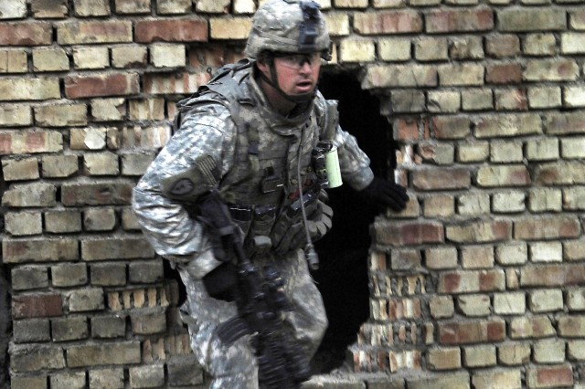 Staff Sgt. Timothy Kees, 2nd Squadron, 2nd Stryker Cavalry Regiment, emerges from a hole in the wall of an abandoned shopping center during a presence patrol in the Dora District of Baghdad, Dec. 14.