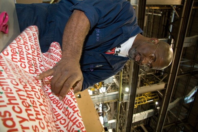 Darry Elston, a heavy mobile equipment mechanic, wraps a pair of sneakers for a child under the care of Department of Human Resources.  Elston and his co-workers on the M113/AVLB production line are providing Christmas gifts for a child as part of Anniston Army Depot's Christmas Cheer program.