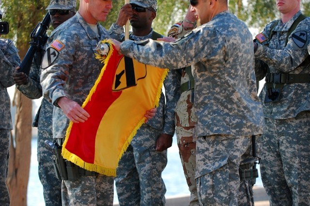 CAMP LIBERTY, Iraq -  Maj. Gen. Joseph Fil, Jr. (left), outgoing Multi-National Division-Baghdad commanding general and Command Sgt. Maj. Philip Johndrow, outgoing MND-B command sergeant major case the 'First Team' colors during the MND-B transfer of authority ceremony Dec. 19 at Camp Liberty, Iraq.