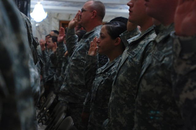 """Soldiers from the Multi-National Division Aca,!"""" Center raise their right hands and re-enlist in the Army during a ceremony Dec. 19 officiated by Army Chief of Staff Gen. George W. Casey Jr."""