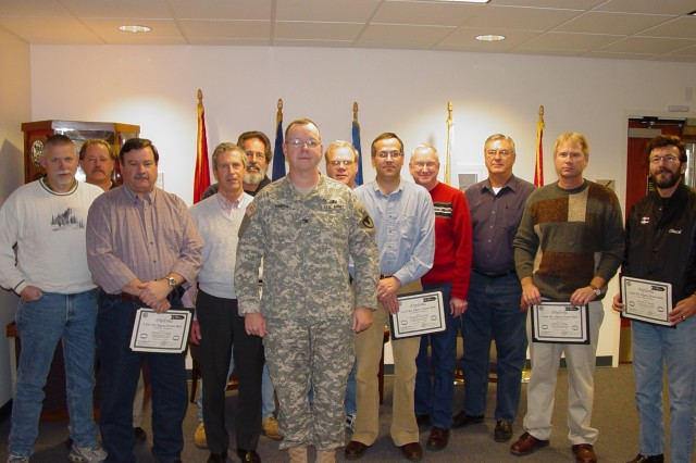 CAAA Commander Col. Charles Kibben (center) presents Green Belt training certificates to CAAA employees Walt Shearin, Bobby Webber, Dennis Sickel, Mike Budarz, Byron Steele, Jerry Tompkins, Randall Burcham, Tom Hedges, Don Neukam, Mark Helms and Chuck Payne.