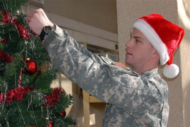 1st Lt. Adam Samiof, Camp Taji, Iraq, helps fellow Soldiers decorate a tree for the holidays.
