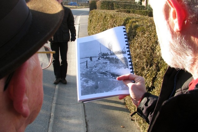 Ted Paluch (left), MalmAfAdy Massacre survivor, compares a wartime photo of the hedgerow where he escaped to freedom.  The shaded portion is a dead U.S. soldier who was shot by Nazi SS troops.