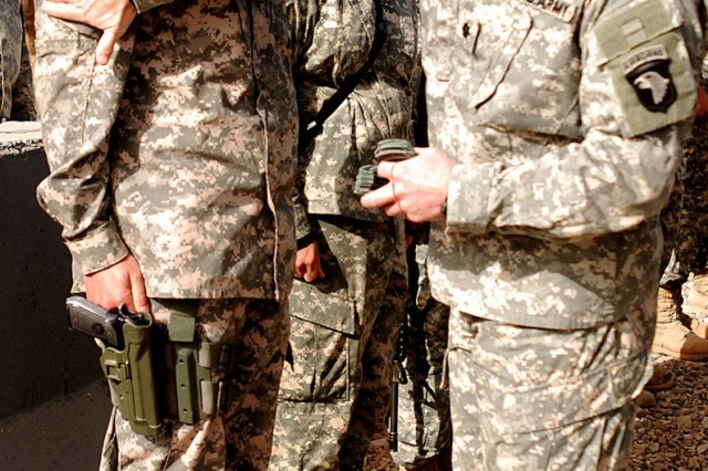 "CAMP LIBERTY, Iraq - Lt. Col. David Burwell, commander of the 1st Battalion, 320th Field Artillery Regiment, 101st Infantry Division 'Top Guns,' places the division's Screaming Eagle unit patch on a Soldier's right shoulder pocket during a ceremony to mark the unit's reception of combat patches at their battalion headquarters Dec. 22. ""Wear these patches with pride,"" Burwell said, ""for they are well-earned."""