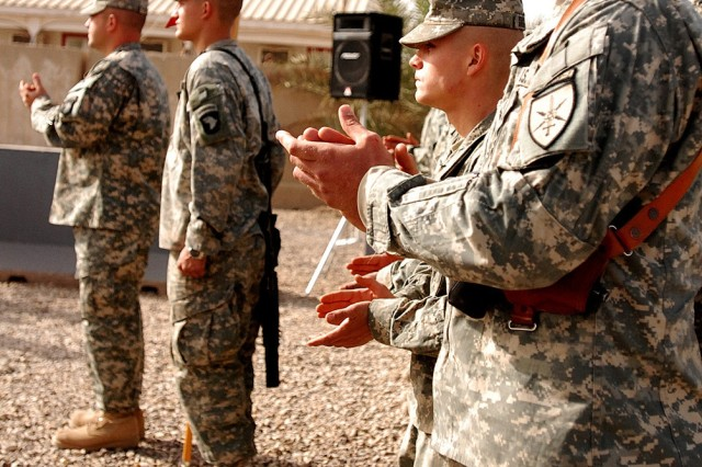 CAMP LIBERTY, Iraq - Soldiers of the Headquarters, Headquarters Battery, 1st Battalion, 320th Field Artillery Regiment, 101st Airborne Division 'Top Guns,' give themselves and the rest of the 'Top Guns' a round of applause at the close of a ceremony to commemorate the day they received their combat patches at their battalion headquarters Dec. 22. Each battery's commander secured a combat patch on his Soldiers' right shoulder pocket, signifying that the Soldiers are now combat veterans.