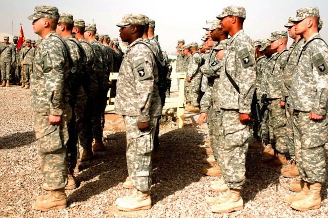 CAMP LIBERTY, Iraq - Soldiers of the Service Battery, 1st Battalion, 320th Field Artillery Regiment, 101st Airborne Division 'Top Guns,' stand in formation after receiving their combat patches during a ceremony at their battalion headquarters Dec. 22. The unit has completed two months of their expected 15-month deployment to Camp Liberty.