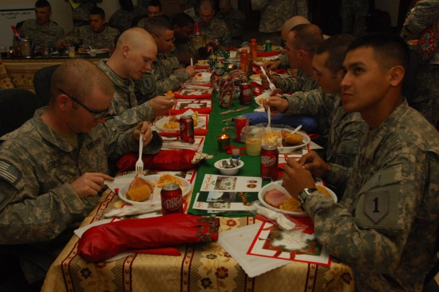 YARMOUK, Iraq-- Soldiers from Battery B, 2nd Battalion, 32nd Field Artillery, attached to 2nd Brigade Combat Team, 101st Airborne Division (Air Assault), enjoy a special holiday meal brought out to the Battery's Christmas party at Joint Security Station Torch in Yarmouk, Iraq, Dec. 25.