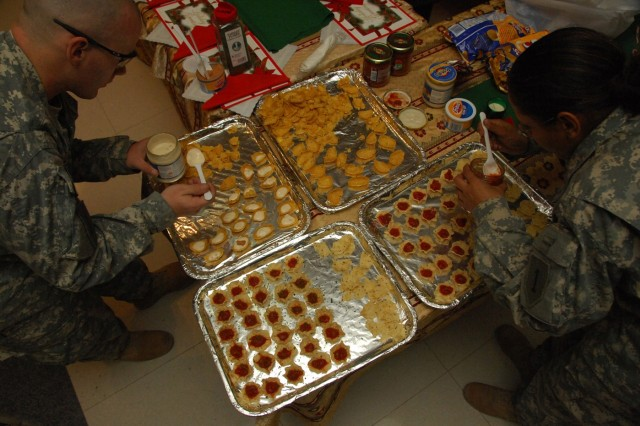 YARMOUK, Iraq-- Soldiers from Battery B, 2nd Battalion, 32nd Field Artillery, attached to 2nd Brigade Combat Team, 101st Airborne Division (Air Assault), prepare snacks at the Battery's Christmas party at Joint Security Station Torch in Yarmouk, Iraq, Dec. 25.