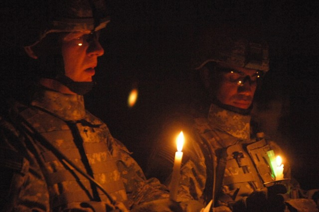 YARMOUK, Iraq-- Chaplain (Capt.) Troy Parson, 2nd Battalion, 32nd Field Artillery, attached to 2nd Brigade Combat Team, 101st Airborne Division (Air Assault), leads Soldiers in a prayer at a candlelight ceremony at the B Battery's Christmas party at Joint Security Station Torch in Yarmouk, Iraq, Dec. 25.