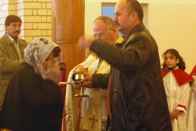 BAGHDAD - A Christian woman from receives Communion from Chaldean Catholic Auxiliary Bishop Shlemon Warduni during Christmas Morning mass at the St. John's Church in Doura. The Church opened its doors again Nov. 15 after closing them in May due to the Al Qaeda and extremist threat in southern Baghdad. Chaldean Christians in the area have attended services regularly since then. (U.S. Army photo by Maj. Kirk Luedeke, 4IBCT, 1ID)