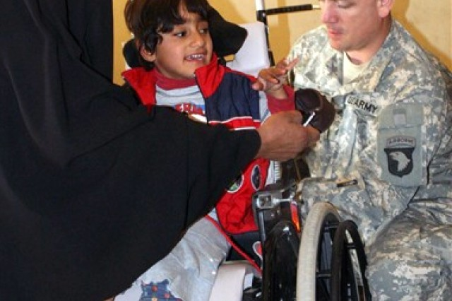 Sgt. Lonnie Todero, a medic with 1st Squadron, 33rd Cavalry, 3rd Brigade Combat Team, 101st Airborne Division (Air Assault), makes adjustments to Zeanib Saad Al Amary's wheelchair Dec. 13, 2007, at Radwaniyah Palace Complex Civil-Military Operations Center in Iraq.