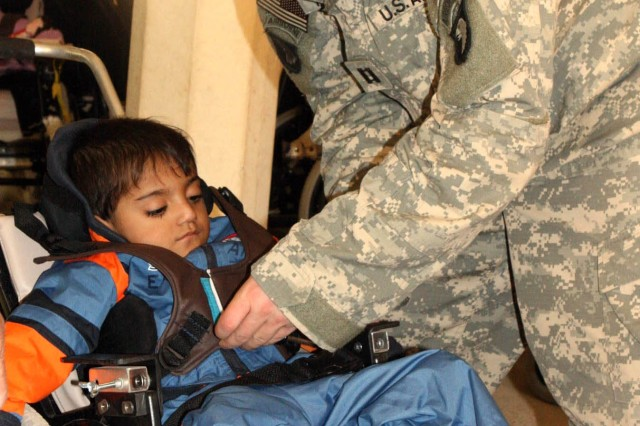 Capt. Seth Palmer, 1st Squadron, 33rd Cavalry, 3rd Brigade Combat Team, 101st Airborne Division (Air Assault), fits Mustafa Murtah, 5, with a new wheelchair Dec. 13, 2007, at the Radwaniyah Palace Complex Civili-Military Operations Center in Iraq.