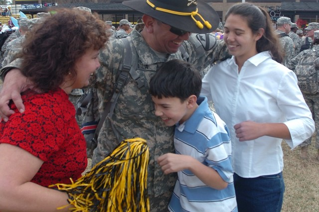 """Dallas native Command Sgt. Maj. Glen Vela, the senior noncommissioned officer for the 615th Aviation Support Battalion, 1st Air Cavalry Brigade, 1st Cavalry Division, gives a great big hug to his wife Kathy (left) and his two kids Andy and Mindy during a welcome home ceremony for about 220 members of the """"Warrior"""" brigade Dec. 21 at Fort Hood's Cooper Field."""