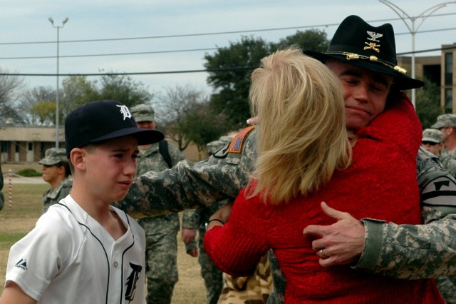 Traverse City, Mich., native Col. Daniel Shanahan, the 1st Air Cavalry Brigade commander, hugs his wife, Mindy, and reaches out for his oldest son, Patrick during the homecoming ceremony held Dec. 21 at 1st Cavalry Division headquarters. Shanahan was one of more than 200 Soldiers in the ceremony who just returned from Iraq.