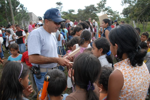COMAYAGUA, Honduras - Herberth Gaekel, 612th Air Base Squadron fire inspector, hands out rulers to Honduran children waiting in line to receive toys from Joint Task Force-Bravo servicemembers here Dec. 23. The toy drive was organized by the JTF-Bravo Chapel and the gifts were donated by the families of servicemembers stationed at Soto Cano Air Base, Honduras.