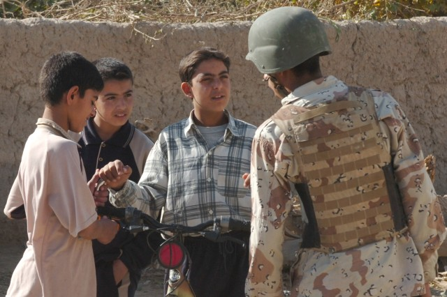 An Iraqi soldier from the 3rd Battalion, 2nd Brigade, 9th Iraqi Army Division (Mechanized) pauses for a moment to speak to some Iraqi boys on the streets of Jerf Al Mila, in northwest Baghdad, Dec. 17 during an event during which Iraqi troops from the 3rd Bn. delivered school supplies and other items to children at a local elementary school.