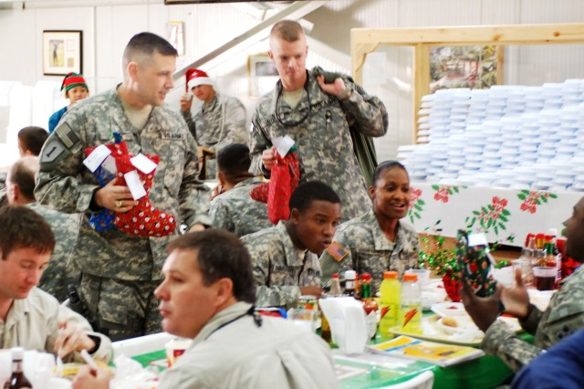 CAMP LIBERTY, Iraq - Buffalo, N.Y., native Command Sgt. Maj. John Gioia, the 4th Infantry Division command sergeant major and the senior non-commissioned officer  with Multi-National Division Baghdad, passes out homemade car-package stockings to Soldiers at the Pegasus Dining Facility here on Christmas day.