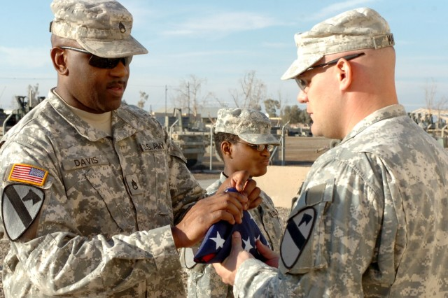 Dallas native Staff Sgt. Stacey Davis, training noncommissioned officer for Headquarters Company, 1st Brigade Special Troops Battalion and 1st Lt. Ross May, battalion operations planner also of the 1st BSTB, who hails from Killeen, Texas fold a flag during a ceremony at Camp Taji, Iraq Dec. 25 commemorating Washington's crossing of the Delaware River on Christmas Day 1776. The flags will be donated as gifts to veterans groups; Soldiers who have done outstanding things in service to their fellow Soldiers as well as to families of military service members killed in action.