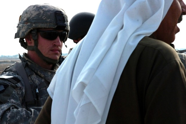 ABU OBAED, Iraq - During a patrol to examine a local bridge, Roseburg, Ore. native Capt. Brian Bassett (left), commander, Company A, 2nd 'Lancer' Battalion, 5th Cavalry Regiment speaks through an interpreter to a local area tribal sheik Dec. 18 about reopening the bridge.