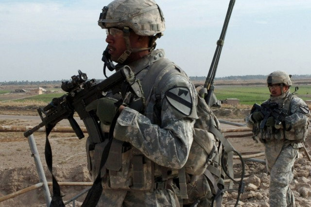 ABU OBAED, Iraq -- Soldiers from Company A, 2nd Battalion, 5th Cavalry Regiment, Clearwater, Fla. native Spc. Lennon Inoa (left), an infantryman, and Staff Sgt. Juan Vargas, a squad leader, who hails from Harlingen, Texas walk past a bridge near here during a Dec. 18 patrol.